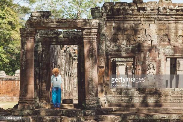 mid adult woman standing in historic building - bortes foto e immagini stock