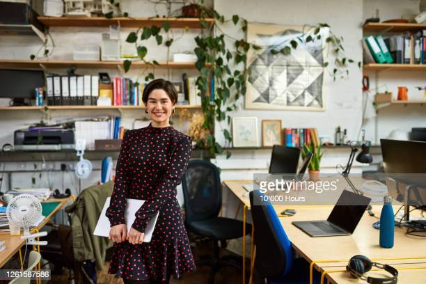 mid adult woman standing in office, smiling at camera - businesswoman stock pictures, royalty-free photos & images