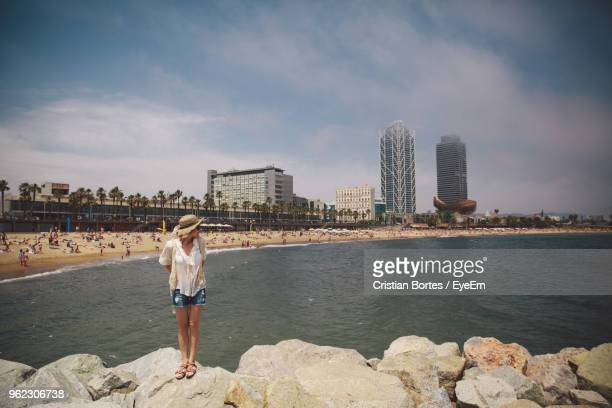 Mid Adult Woman Standing On Rocks By Sea