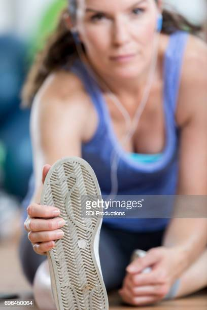 Mid adult woman stretches leg before excercise