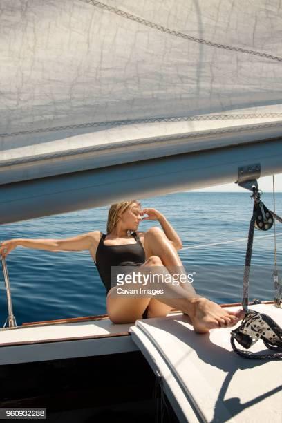 Mid adult woman sunbathing on yacht