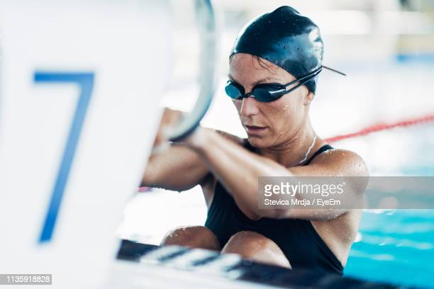 mid adult woman swimming in pool - schwimmen stock-fotos und bilder