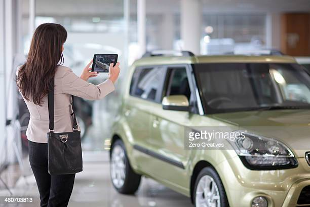 Mid adult woman taking photograph of car in showroom