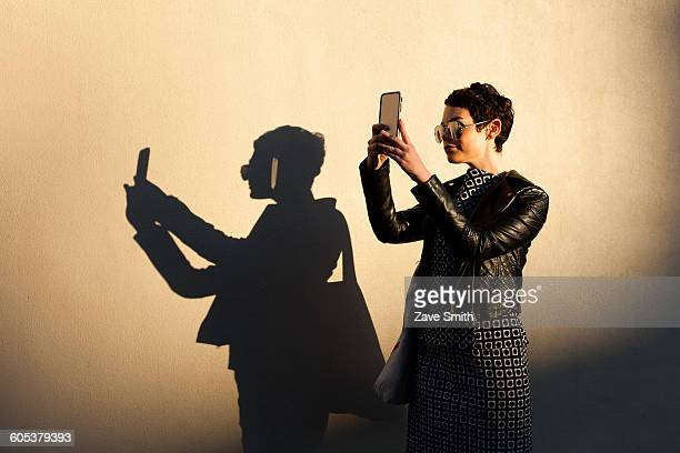 mid adult woman taking self portrait, using smartphone, shadow cast on wall beside her - hitech mod a stock pictures, royalty-free photos & images