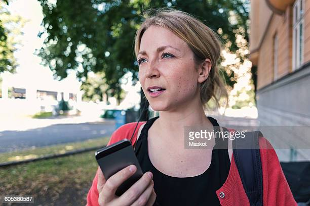 Mid adult woman talking on mobile phone while walking on sidewalk