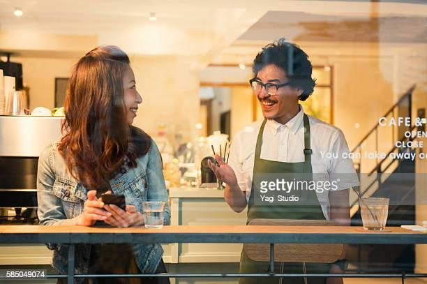 mid adult woman talking with a cafe of the varistor - gastronomiebetrieb stock-fotos und bilder