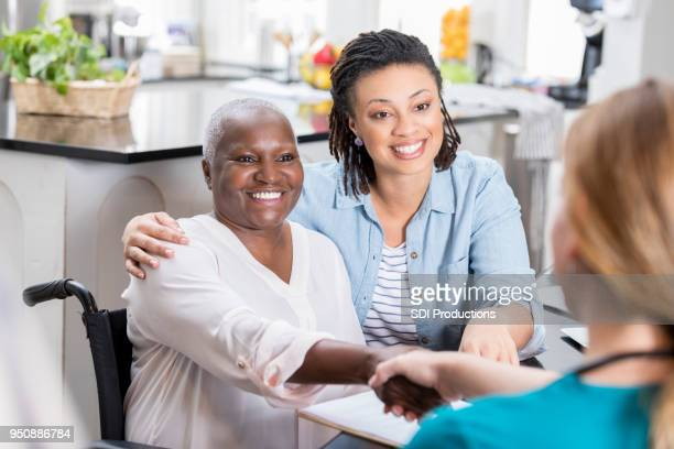Mid adult woman talks with her mom's nurse