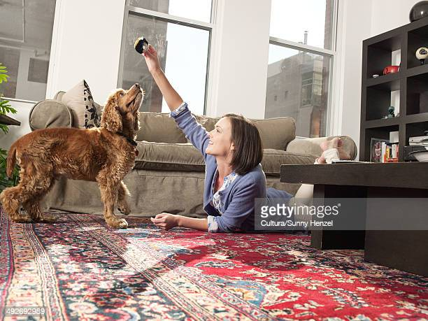 Mid adult woman teching pet dog in living room