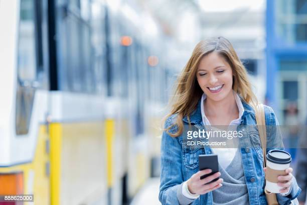 Mid adult woman texts after getting off of commuter train