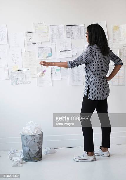 Mid adult woman throwing away crumpled paper ball