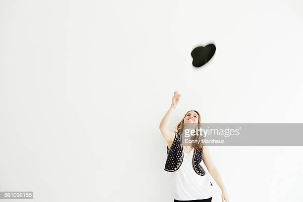 Mid adult woman throwing hat in the air, copy space