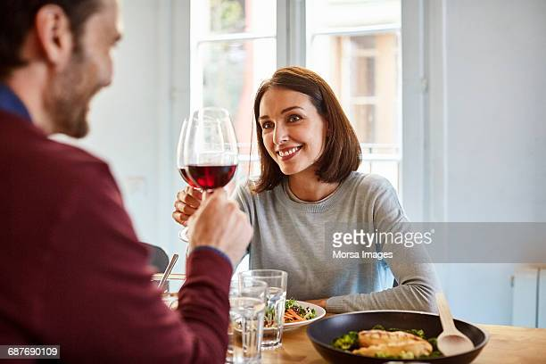mid adult woman toasting wine glass with man - woman sitting on man's lap stock pictures, royalty-free photos & images