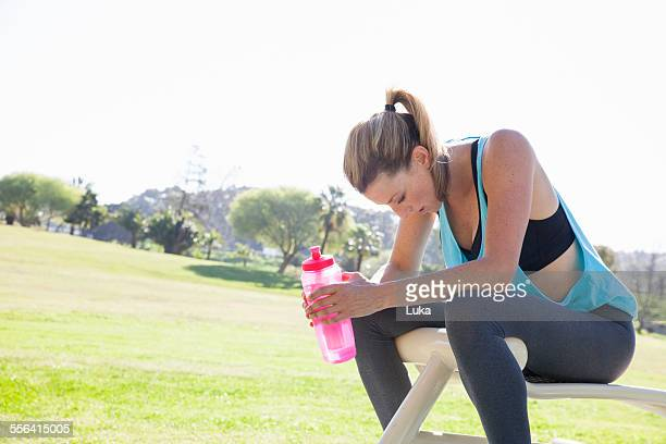 Mid adult woman training in park drinking water bottle
