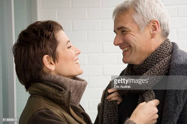 Mid adult woman tying a mature man's scarf