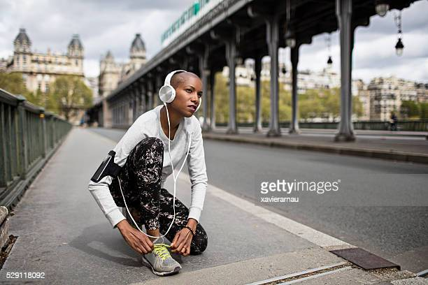 Mid adult woman tying the shoelaces before running in Paris