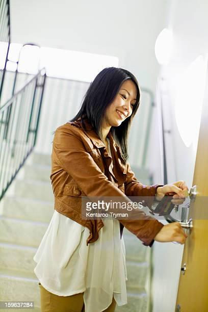 Mid adult woman unlocking door with keys