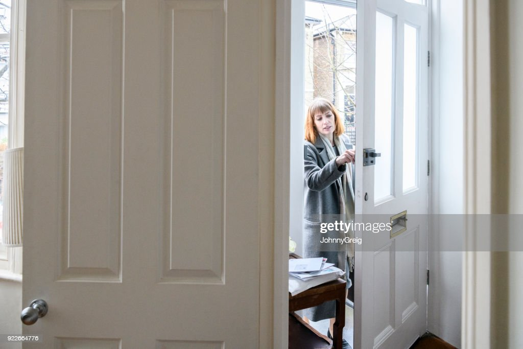 Mid adult woman unlocking front door and arriving home : Stock Photo