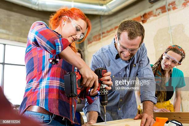 Mid adult woman uses power drill in makerspace