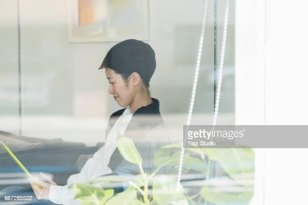 30 代の女性は、美容室でデジタル タブレットを使用します。