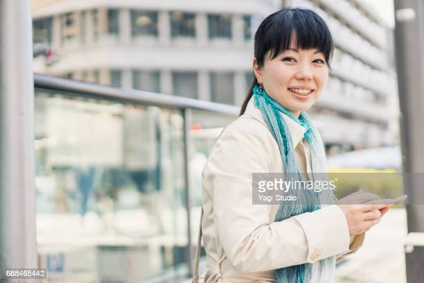 mid adult woman using a smartphone in the city. - one mid adult woman only stock pictures, royalty-free photos & images