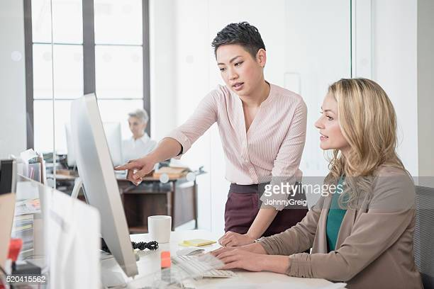 mid adult woman using computer, young woman pointing - pointing stock photos and pictures