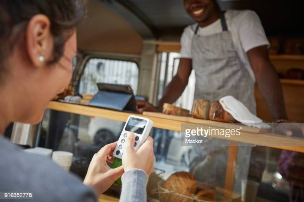 mid adult woman using credit card reader to pay salesman at food truck - finance and economy stock pictures, royalty-free photos & images