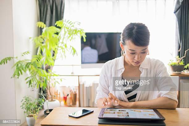 30 代の女性のデジタルタブレットを使用して自宅で