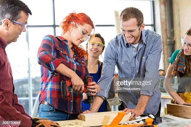 Frau mittleren Alters mit Bohrmaschine in Workshops