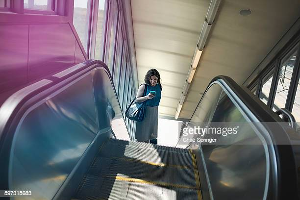 Mid adult woman using escalator, holding smartphone, elevated view