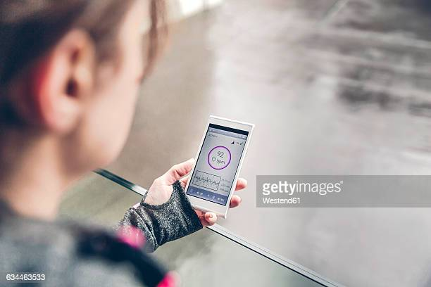 Mid adult woman using heatr rate monitor app on smart phone