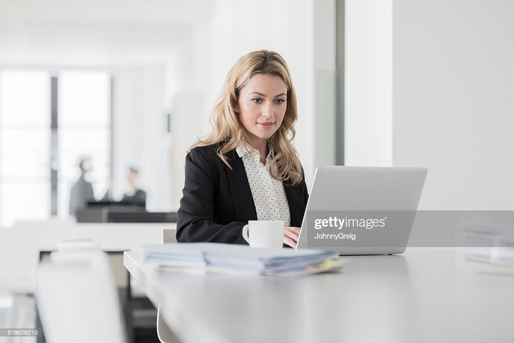 Mid adult woman using laptop and concentrating in office : Stock Photo