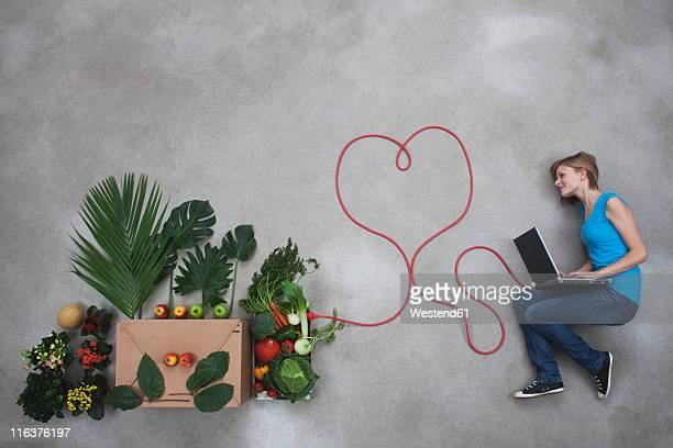 Mid adult woman using laptop and electric cable connected to vegetable box