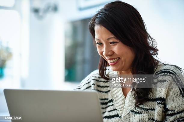 mid adult woman using laptop and smiling - video conference stock pictures, royalty-free photos & images