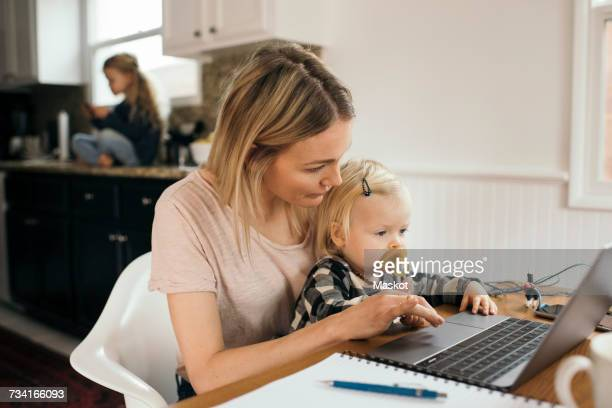 mid adult woman using laptop while daughter sitting on her lap at home - home icon stock photos and pictures