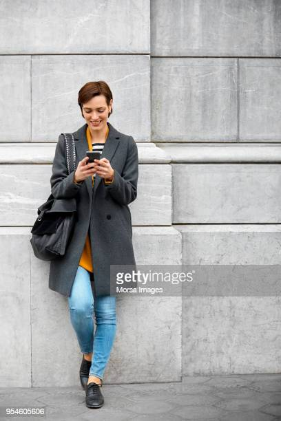 mid adult woman using mobile phone against wall - grey purse stock pictures, royalty-free photos & images