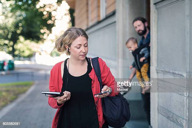 Mid adult woman using mobile phone while leaving for work with family in background