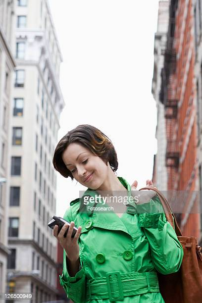 mid adult woman using pda on street, low angle view - low angle view photos et images de collection