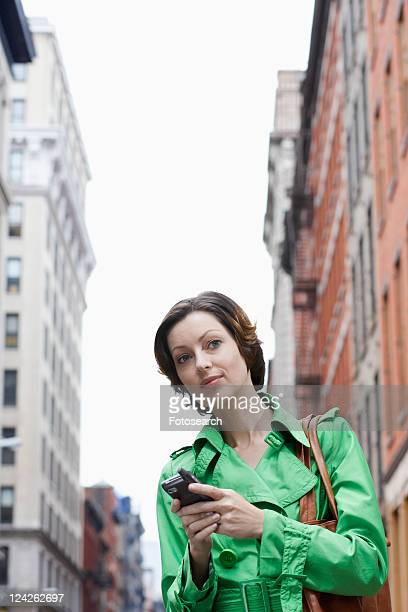 Mid adult woman using PDA on street