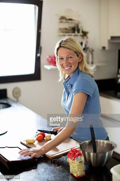 Mid adult woman using recipe on digital table and making meal in kitchen