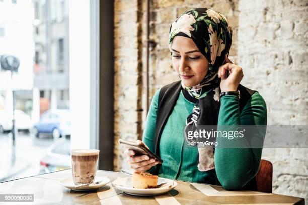 mid adult woman using smartphone in cafe - headscarf stock pictures, royalty-free photos & images