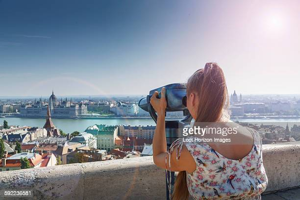 Mid adult woman using viewing binoculars, rear view, Budapest, Hungary