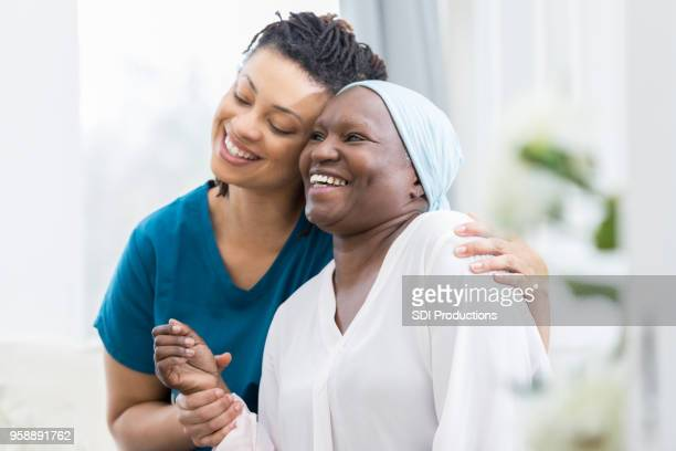 mid adult woman visits her elderly mother - cancer stock photos and pictures