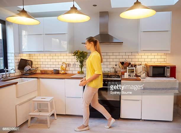 Mid adult woman walking in stylish kitchen