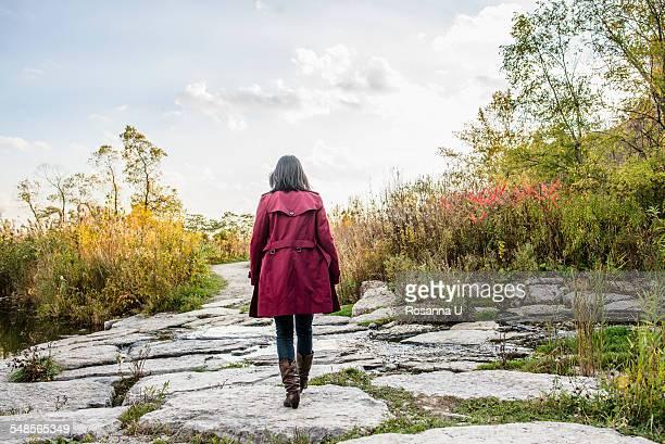 mid adult woman walking on rocks, rear view - frau von hinten stock-fotos und bilder