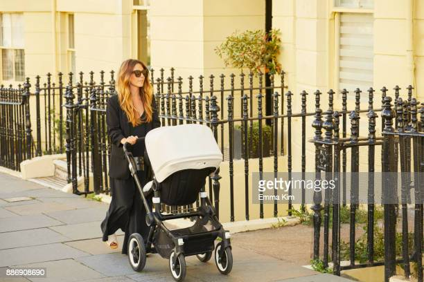 Mid adult woman walking outdoors, pushing pram