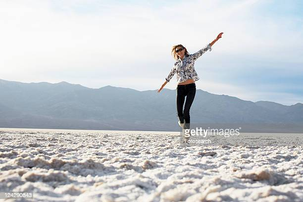 Mid adult woman walking with arms outstretched in desert