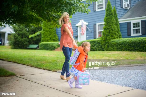 Mid adult woman walking with eager daughter on suburban sidewalk
