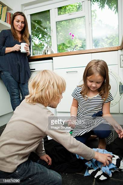 Mid adult woman watching children sort laundry