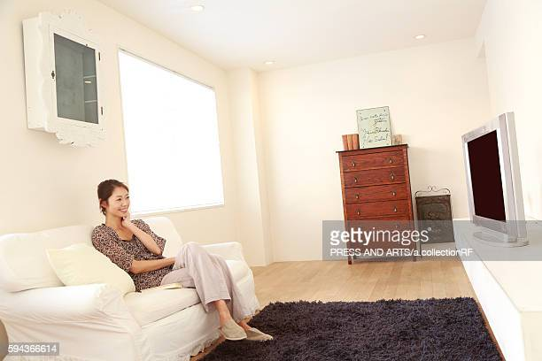 Mid adult woman watching TV