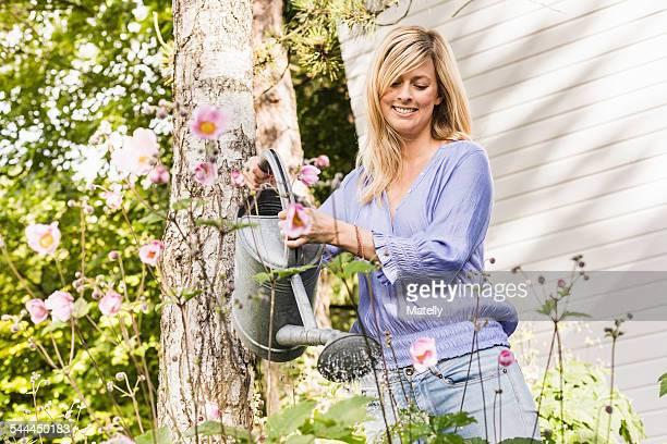 Mid adult woman watering flowers in garden